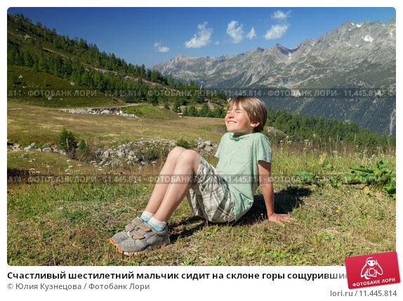 Счастливый шестилетний мальчик сидит на склоне горы сощурившись на солнышке. Стоковое фото, фотограф Юлия Кузнецова / Фотобанк Лори