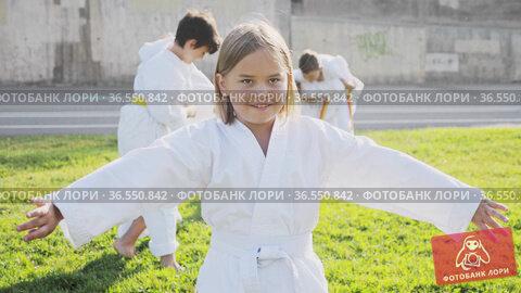 Schoolgirl eight years old in kimono with white belt exercising karate at summer park. Стоковое видео, видеограф Яков Филимонов / Фотобанк Лори