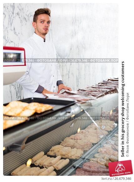 Купить «Seller in his grocery shop welcoming customers», фото № 26679346, снято 19 апреля 2019 г. (c) Яков Филимонов / Фотобанк Лори