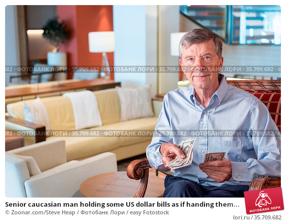 Senior caucasian man holding some US dollar bills as if handing them... Стоковое фото, фотограф Zoonar.com/Steve Heap / easy Fotostock / Фотобанк Лори