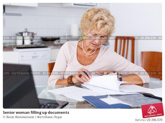 Купить «Senior woman filling up documents», фото № 29396570, снято 11 июля 2018 г. (c) Яков Филимонов / Фотобанк Лори
