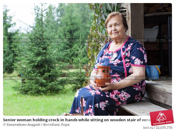 Senior woman holding crock in hands while sitting on wooden stair of veranda, timber house in countryside, copyspace. Стоковое фото, фотограф Кекяляйнен Андрей / Фотобанк Лори