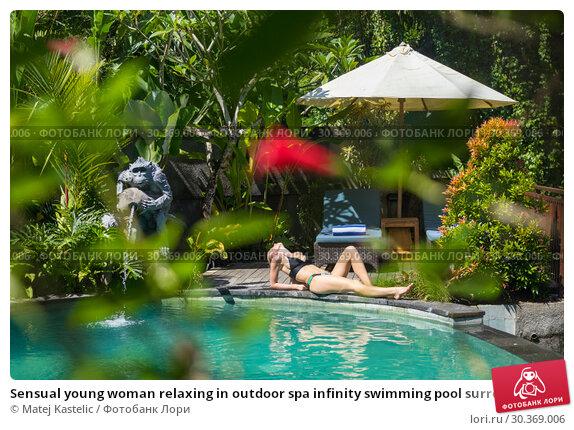 Купить «Sensual young woman relaxing in outdoor spa infinity swimming pool surrounded with lush tropical greenery of Ubud, Bali.», фото № 30369006, снято 22 февраля 2019 г. (c) Matej Kastelic / Фотобанк Лори
