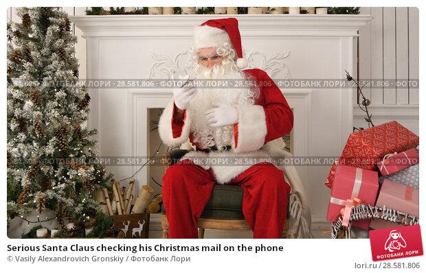 Купить «Serious Santa Claus checking his Christmas mail on the phone», фото № 28581806, снято 25 июня 2018 г. (c) Vasily Alexandrovich Gronskiy / Фотобанк Лори