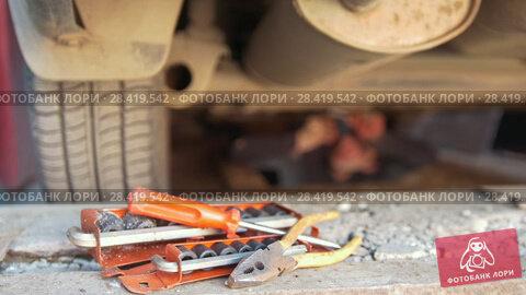 Купить «Set of tools in front of man underneath a car unscrewing details from under tray», видеоролик № 28419542, снято 24 мая 2018 г. (c) Константин Шишкин / Фотобанк Лори
