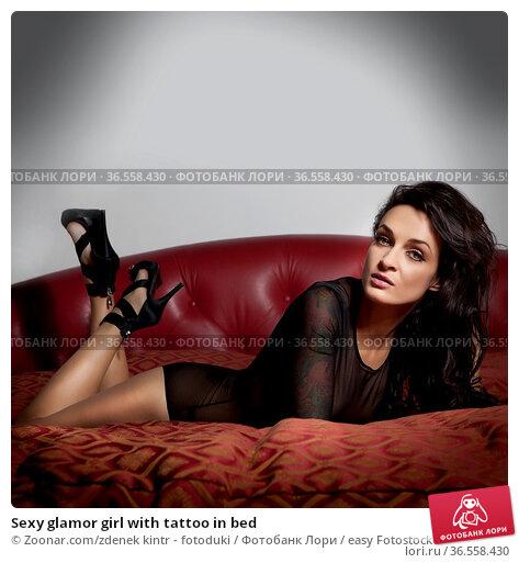 Sexy glamor girl with tattoo in bed. Стоковое фото, фотограф Zoonar.com/zdenek kintr - fotoduki / easy Fotostock / Фотобанк Лори