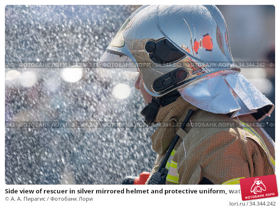 Side view of rescuer in silver mirrored helmet and protective uniform, water drops falling on firefighter Emercom of Russian Federation MChS (2019 год). Редакционное фото, фотограф А. А. Пирагис / Фотобанк Лори