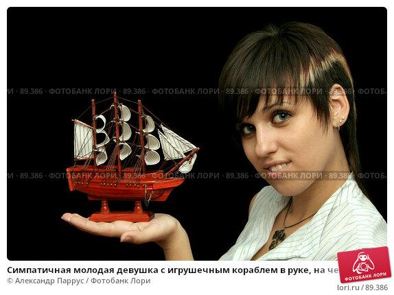 Симпатичная молодая девушка с игрушечным кораблем в руке, на черном фоне, фото № 89386, снято 31 мая 2007 г. (c) Александр Паррус / Фотобанк Лори
