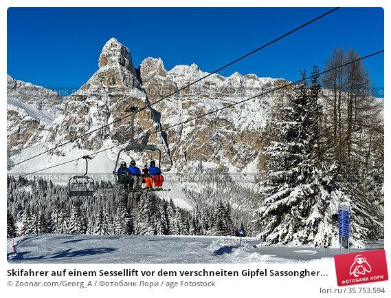 Skifahrer auf einem Sessellift vor dem verschneiten Gipfel Sassongher... Стоковое фото, фотограф Zoonar.com/Georg_A / age Fotostock / Фотобанк Лори