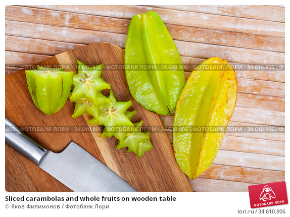 Sliced carambolas and whole fruits on wooden table. Стоковое фото, фотограф Яков Филимонов / Фотобанк Лори