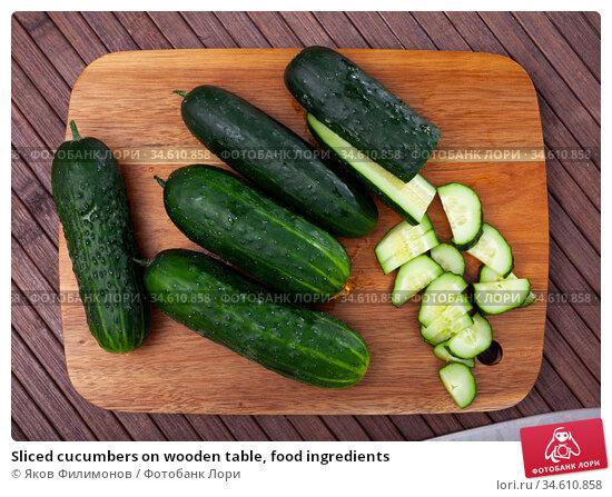 Sliced cucumbers on wooden table, food ingredients. Стоковое фото, фотограф Яков Филимонов / Фотобанк Лори