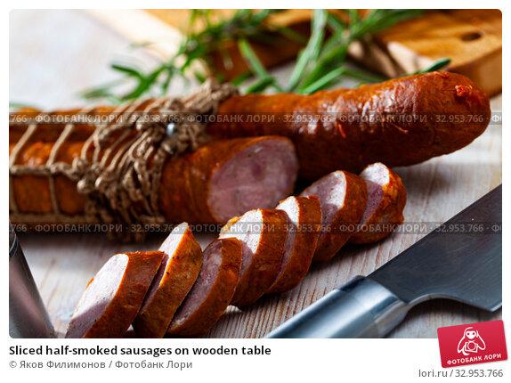 Sliced half-smoked sausages on wooden table. Стоковое фото, фотограф Яков Филимонов / Фотобанк Лори