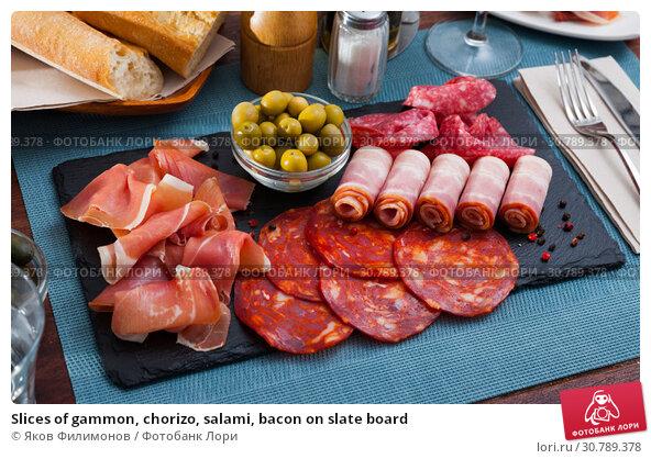 Купить «Slices of gammon, chorizo, salami, bacon on slate board», фото № 30789378, снято 26 июня 2019 г. (c) Яков Филимонов / Фотобанк Лори