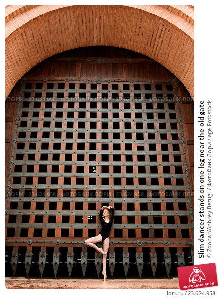 Купить «Slim dancer stands on one leg near the old gate», фото № 23624958, снято 17 февраля 2019 г. (c) age Fotostock / Фотобанк Лори