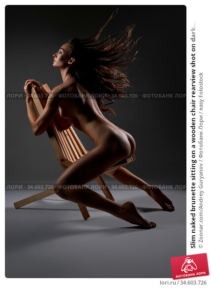 Slim naked brunette sitting on a wooden chair rearview shot on dark... Стоковое фото, фотограф Zoonar.com/Andrey Guryanov / easy Fotostock / Фотобанк Лори