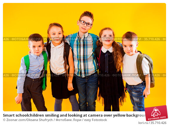 Smart schoolchildren smiling and looking at camera over yellow background... Стоковое фото, фотограф Zoonar.com/Oksana Shufrych / easy Fotostock / Фотобанк Лори