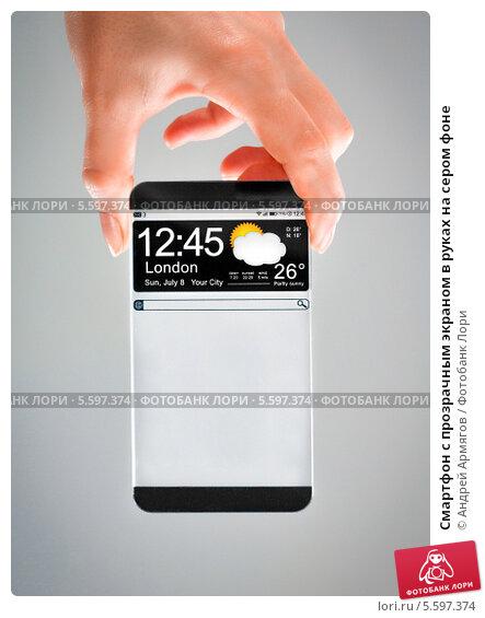 Купить «Смартфон с прозрачным экраном в руках на сером фоне», фото № 5597374, снято 9 января 2014 г. (c) Андрей Армягов / Фотобанк Лори