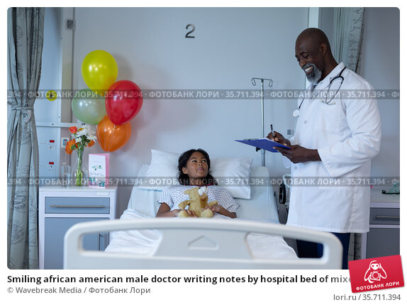 Smiling african american male doctor writing notes by hospital bed of mixed race sick girl patient. Стоковое фото, агентство Wavebreak Media / Фотобанк Лори