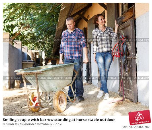 Купить «Smiling couple with barrow standing at horse stable outdoor», фото № 29464782, снято 4 июля 2018 г. (c) Яков Филимонов / Фотобанк Лори