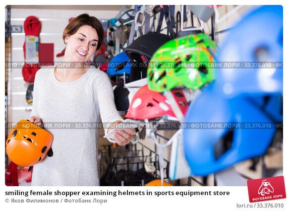 Купить «smiling female shopper examining helmets in sports equipment store», фото № 33376010, снято 24 февраля 2017 г. (c) Яков Филимонов / Фотобанк Лори