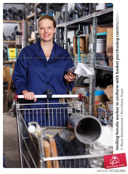Купить «Smiling female worker in uniform with basket purchasing construction materials», фото № 30528686, снято 20 сентября 2018 г. (c) Яков Филимонов / Фотобанк Лори
