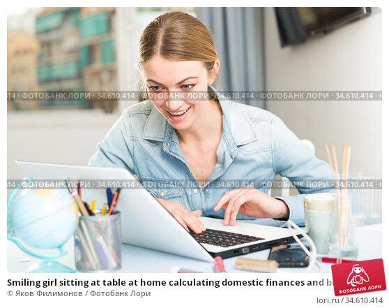 Smiling girl sitting at table at home calculating domestic finances and bills. Стоковое фото, фотограф Яков Филимонов / Фотобанк Лори