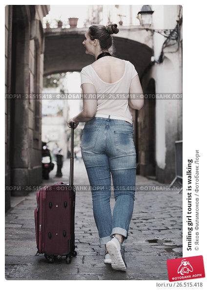 Купить «Smiling girl tourist is walking», фото № 26515418, снято 4 мая 2017 г. (c) Яков Филимонов / Фотобанк Лори