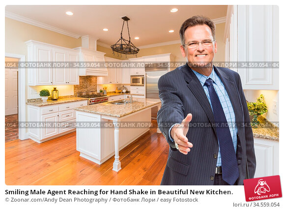 Smiling Male Agent Reaching for Hand Shake in Beautiful New Kitchen. Стоковое фото, фотограф Zoonar.com/Andy Dean Photography / easy Fotostock / Фотобанк Лори