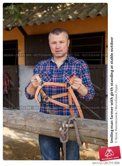 Купить «Smiling man farmer with girth standing at stable outdoor», фото № 29711094, снято 4 июля 2018 г. (c) Яков Филимонов / Фотобанк Лори