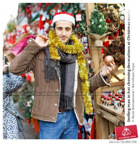 Smiling man in hat choosing decorations at Christmas market. Стоковое фото, фотограф Яков Филимонов / Фотобанк Лори