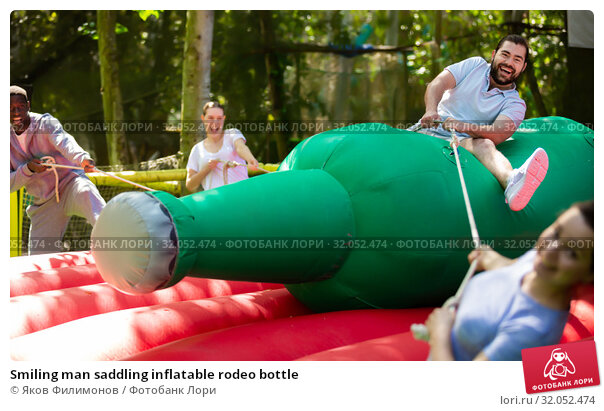 Smiling man saddling inflatable rodeo bottle. Стоковое фото, фотограф Яков Филимонов / Фотобанк Лори