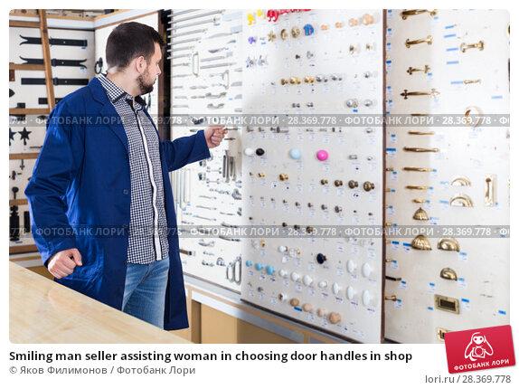 Купить «Smiling man seller assisting woman in choosing door handles in shop», фото № 28369778, снято 5 апреля 2017 г. (c) Яков Филимонов / Фотобанк Лори