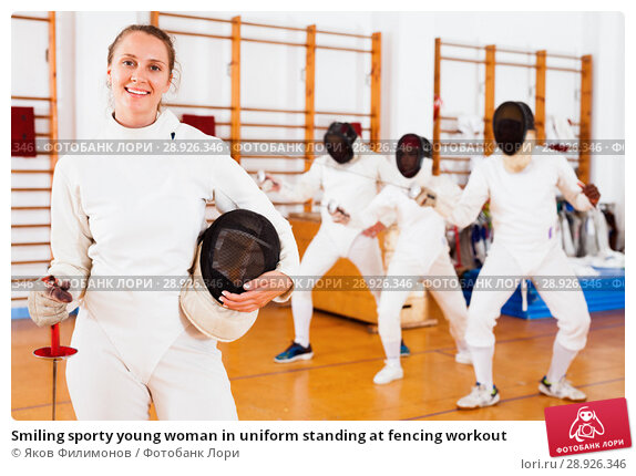 Купить «Smiling sporty young woman in uniform standing at fencing workout», фото № 28926346, снято 11 июля 2018 г. (c) Яков Филимонов / Фотобанк Лори