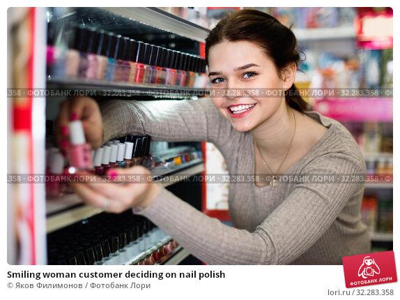 Купить «Smiling woman customer deciding on nail polish», фото № 32283358, снято 21 февраля 2017 г. (c) Яков Филимонов / Фотобанк Лори