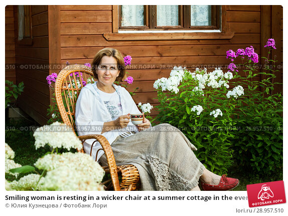 Купить «Smiling woman is resting in a wicker chair at a summer cottage in the evening», фото № 28957510, снято 4 августа 2018 г. (c) Юлия Кузнецова / Фотобанк Лори