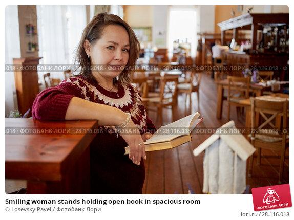 Купить «Smiling woman stands holding open book in spacious room», фото № 28116018, снято 4 февраля 2017 г. (c) Losevsky Pavel / Фотобанк Лори