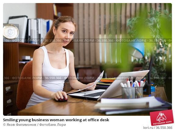 Smiling young business woman working at office desk. Стоковое фото, фотограф Яков Филимонов / Фотобанк Лори