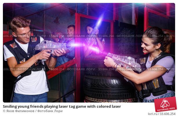 Купить «Smiling young friends playing laser tag game with colored laser», фото № 33606254, снято 23 августа 2018 г. (c) Яков Филимонов / Фотобанк Лори