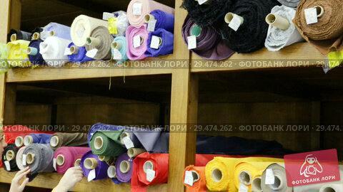 Купить «Smiling young woman choosing textiles for dressmaking in fabric shop», видеоролик № 29474262, снято 28 марта 2018 г. (c) Яков Филимонов / Фотобанк Лори