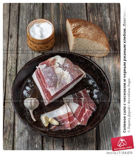 Купить «Соленое сало с чесноком и черным ржаным хлебом. Ломтики сала с чесноком на чугунной сковороде», фото № 7154870, снято 22 марта 2015 г. (c) Лариса Дерий / Фотобанк Лори