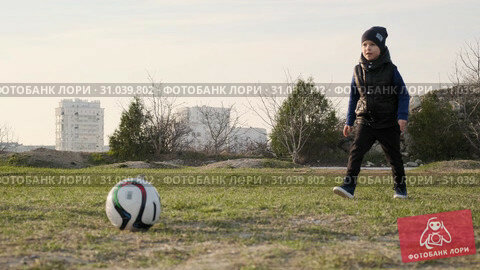 Son takes the ball and kicks it to his dad playing football in early spring slow motion. Стоковое видео, видеограф Denis Mishchenko / Фотобанк Лори
