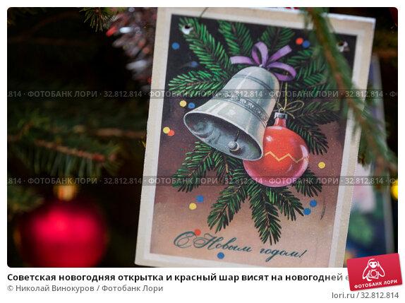 Купить «Советская новогодняя открытка и красный шар висят на новогодней елке», фото № 32812814, снято 31 декабря 2019 г. (c) Николай Винокуров / Фотобанк Лори