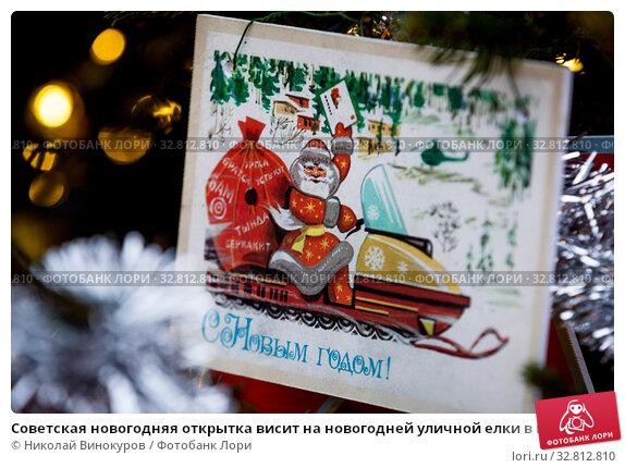 Купить «Советская новогодняя открытка висит на новогодней уличной елки в центре города Москвы», фото № 32812810, снято 31 декабря 2019 г. (c) Николай Винокуров / Фотобанк Лори