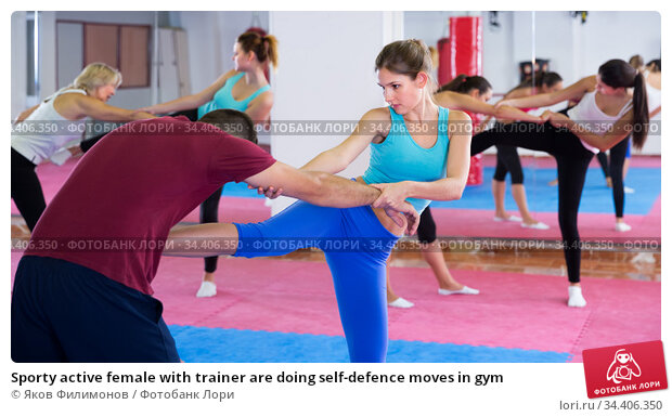 Sporty active female with trainer are doing self-defence moves in gym. Стоковое фото, фотограф Яков Филимонов / Фотобанк Лори