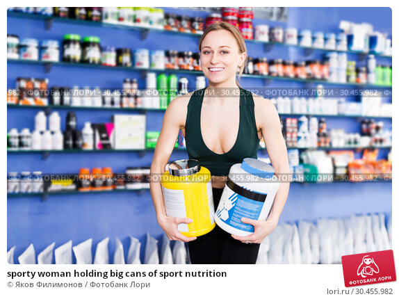 sporty woman holding big cans of sport nutrition. Стоковое фото, фотограф Яков Филимонов / Фотобанк Лори