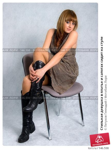 Купить «Стильная девушка в платье и сапогах сидит на стуле», фото № 146598, снято 1 декабря 2007 г. (c) Петухов Геннадий / Фотобанк Лори