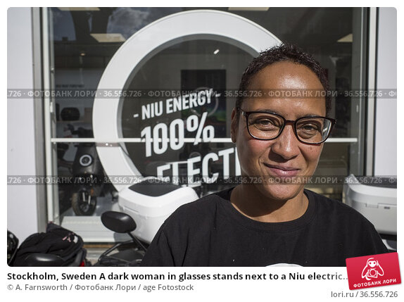 Stockholm, Sweden A dark woman in glasses stands next to a Niu electric... Редакционное фото, фотограф A. Farnsworth / age Fotostock / Фотобанк Лори