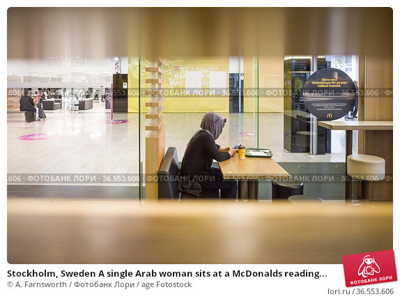 Stockholm, Sweden A single Arab woman sits at a McDonalds reading... Редакционное фото, фотограф A. Farnsworth / age Fotostock / Фотобанк Лори