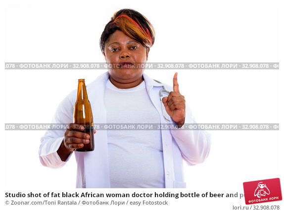 Studio shot of fat black African woman doctor holding bottle of beer and pointing finger up. Стоковое фото, фотограф Zoonar.com/Toni Rantala / easy Fotostock / Фотобанк Лори
