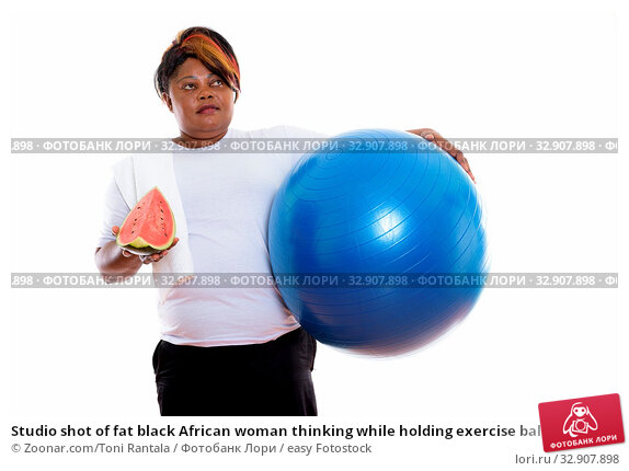 Studio shot of fat black African woman thinking while holding exercise ball and slice of watermelon ready for gym. Стоковое фото, фотограф Zoonar.com/Toni Rantala / easy Fotostock / Фотобанк Лори